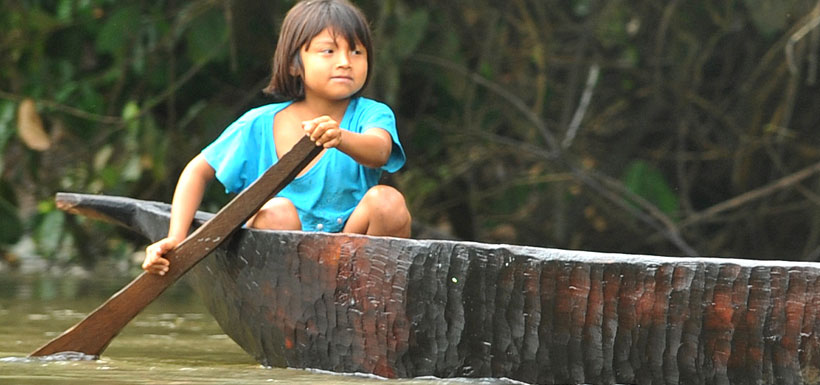 Young child paddling canoe